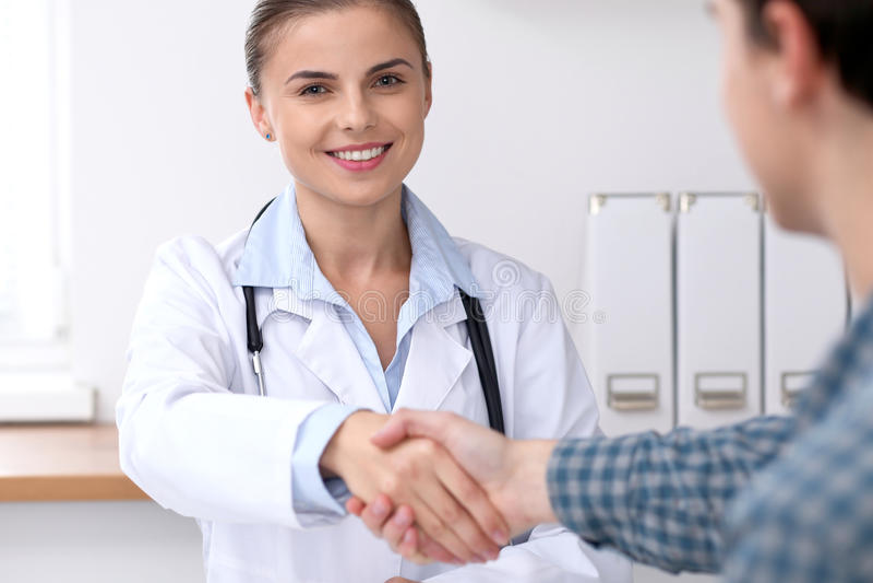 Medique a mulher que sorri ao agitar as mãos com seu paciente masculino Conceito da medicina e da confiança foto de stock royalty free