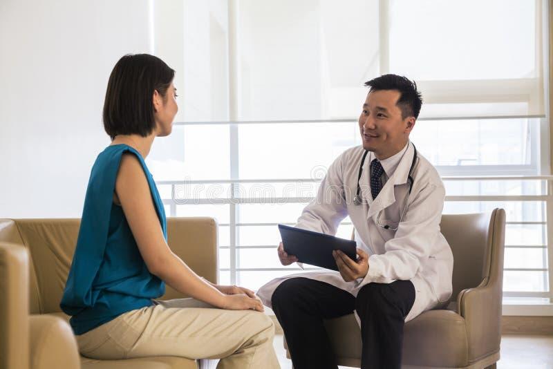 Medique o assento para baixo e o paciente de consulta no hospital imagens de stock