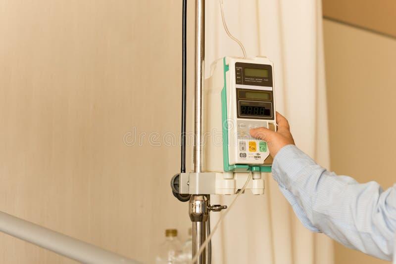 Medique o controle IV da mão do ` s no gotejamento do intravenous IV da bomba da infusão mim imagem de stock