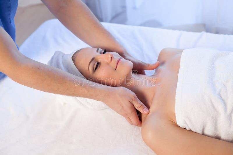 Medique o cosmetologist que faz tratamentos faciais dos termas da menina da massagem fotografia de stock royalty free