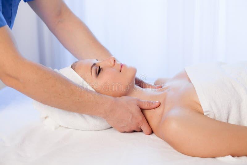 Medique o cosmetologist que faz tratamentos faciais dos termas da menina da massagem imagens de stock