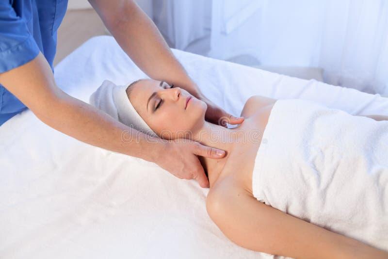 Medique o cosmetologist que faz tratamentos faciais dos termas da menina da massagem foto de stock