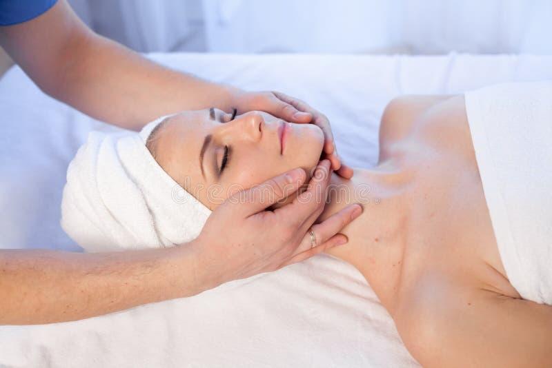 Medique o cosmetologist que faz tratamentos faciais dos termas da menina da massagem imagens de stock royalty free