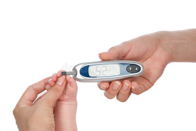 Medique o dedo infantil da criança do bebê do diabetes da picada para o açúcar da glicose que mede a análise de sangue nivelada foto de stock
