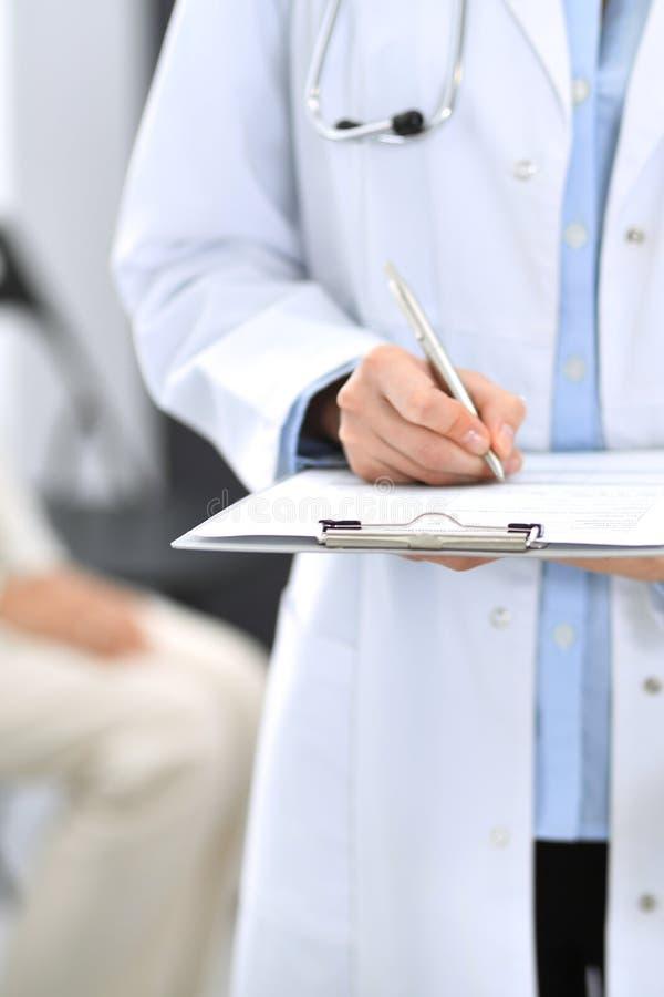 Medique o enchimento da mulher acima do formulário médico ao estar perto da mesa de recepção na clínica ou no hospital da emergên imagens de stock