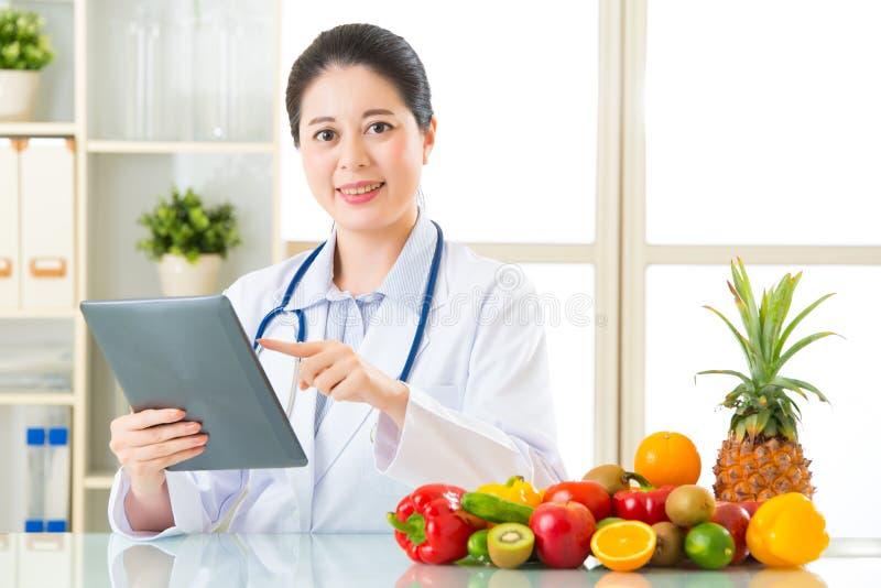 Medique o nutricionista que usa a tabuleta digital com frutos e vegetab foto de stock