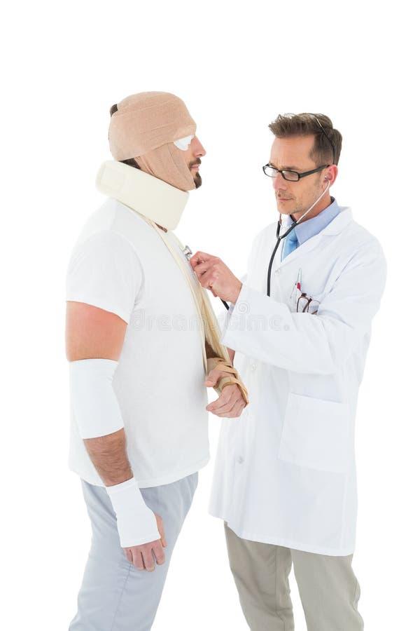 Medique o paciente auscultating amarrado acima na atadura com estetoscópio foto de stock royalty free