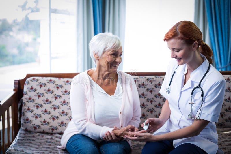 Medique o teste de um nível da glicose dos pacientes usando um glucometer digital imagens de stock
