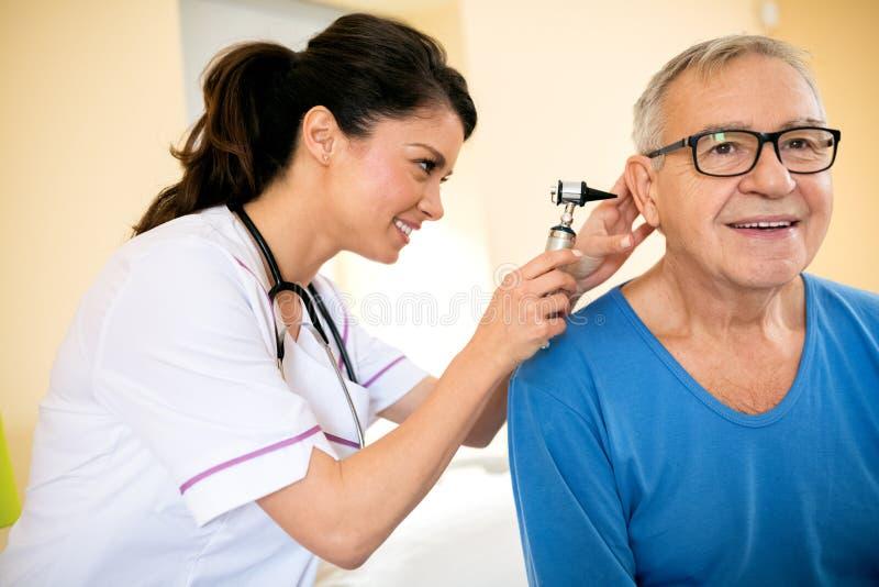 Medique a orelha do exame com o otoscope na clínica do lar de idosos imagens de stock royalty free