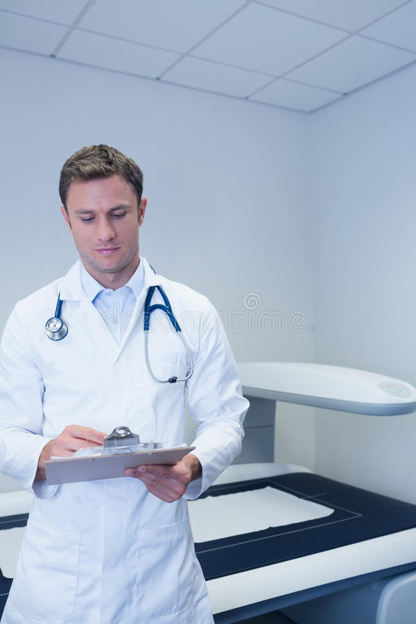 Medique a posição na frente da escrita da máquina de raio X algo imagem de stock