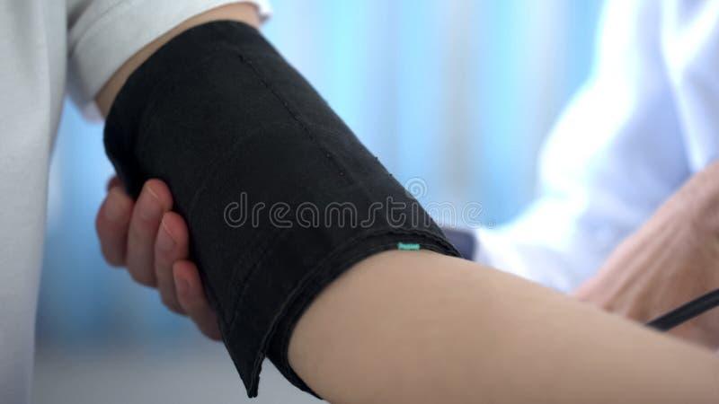 Medique a pressão sanguínea de medição do paciente fêmea com sphygmomanometer, close up fotos de stock royalty free