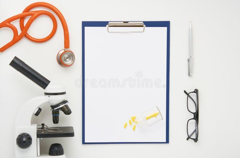 Medique a tabela com microscópio, estetoscópio e vidros, vista superior fotos de stock royalty free