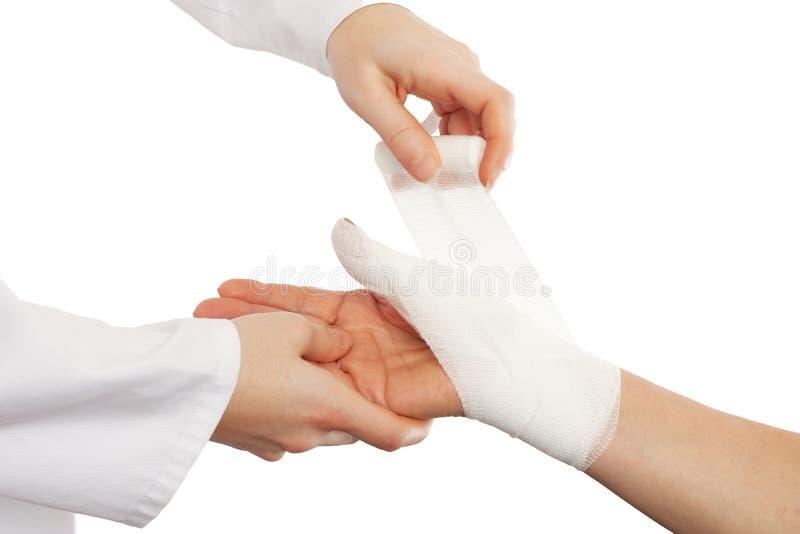 Medique a tampa a mão do paciente pela atadura fotografia de stock