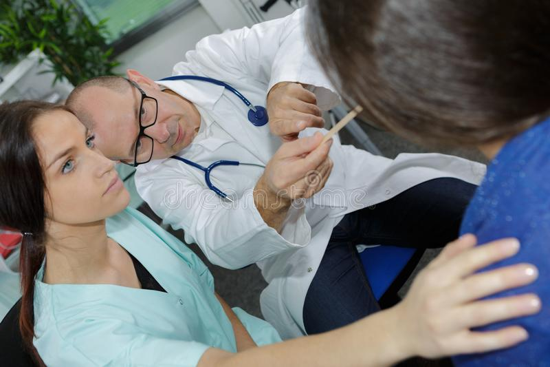 Medique usando o depressor de língua para examinar o paciente da garganta foto de stock royalty free