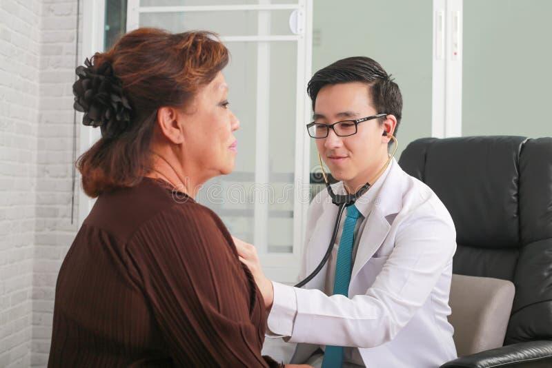 Medique usando o estetoscópio ao coração do paciente da mulher do exame foto de stock