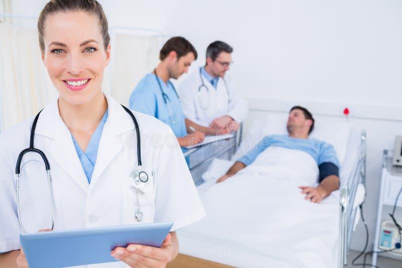 Medique usando a tabuleta digital com colegas e paciente atrás fotografia de stock