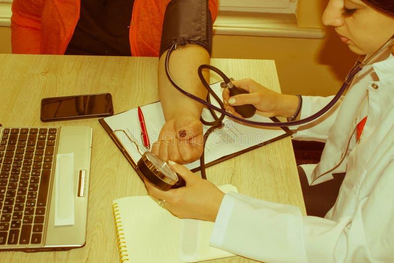 Medique a verificação da pressão sanguínea de um paciente, ele está medindo pulsos com um sphygmomanometer, conceito do coração d imagem de stock
