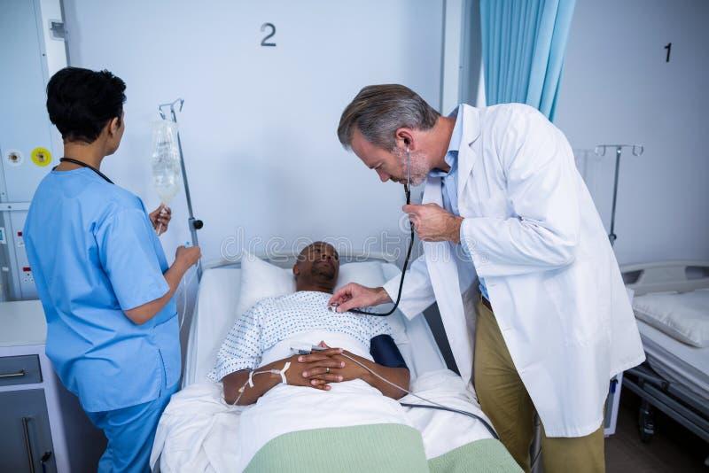 Medique a verificação da pulsação do coração paciente com o estetoscópio na divisão imagens de stock