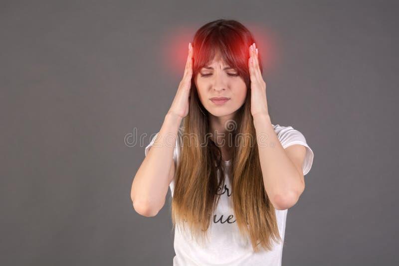 Medisch concept over hoofdpijn Het meisje houdt haar handen op haar tempels royalty-vrije stock afbeeldingen