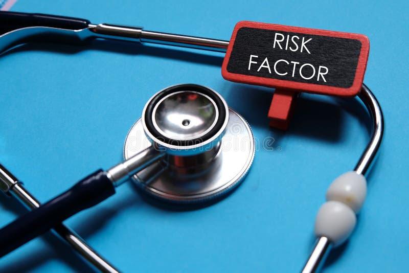 MEDISCH concept Stethoscoop op blauwe achtergrond met houten die teken met RISICOfactor wordt geschreven royalty-vrije stock foto