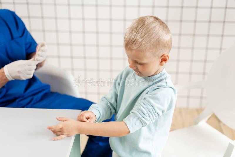 Medisch flard De arts in blauwe die eenvormig maakt elastiek rond een jongenshand wordt verbonden met trauma in zijn wapen In het royalty-vrije stock foto's