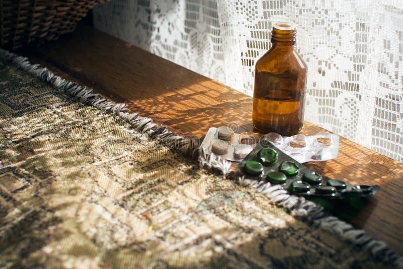 Medisch fles en pillenflesje met geneeskunde op een houten lijst, medicijnen van een oude vrouw royalty-vrije stock afbeeldingen