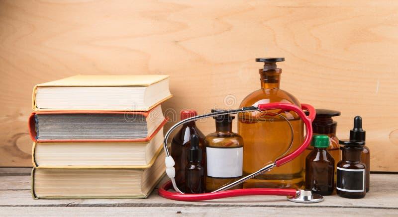 Medisch onderwijsconcept - boeken, apotheekflessen en stethoscoop stock foto