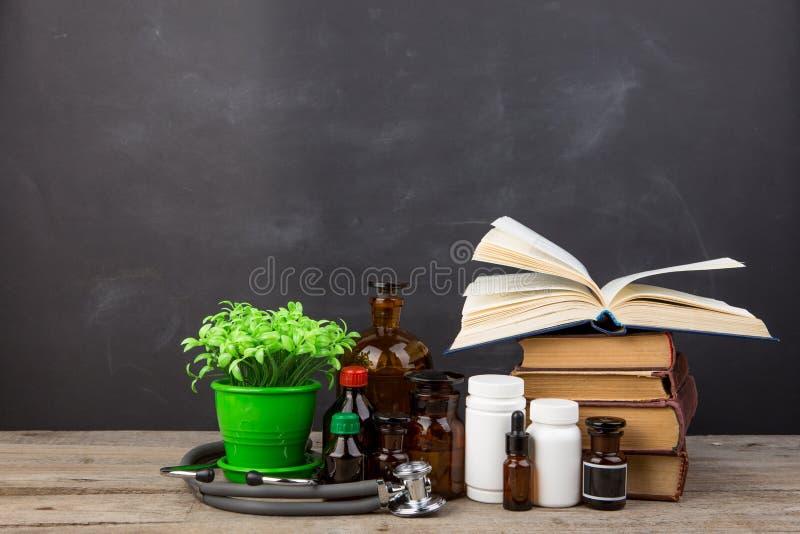 Medisch onderwijsconcept - boeken, apotheekflessen, stethoscoop in het auditorium met bord royalty-vrije stock fotografie