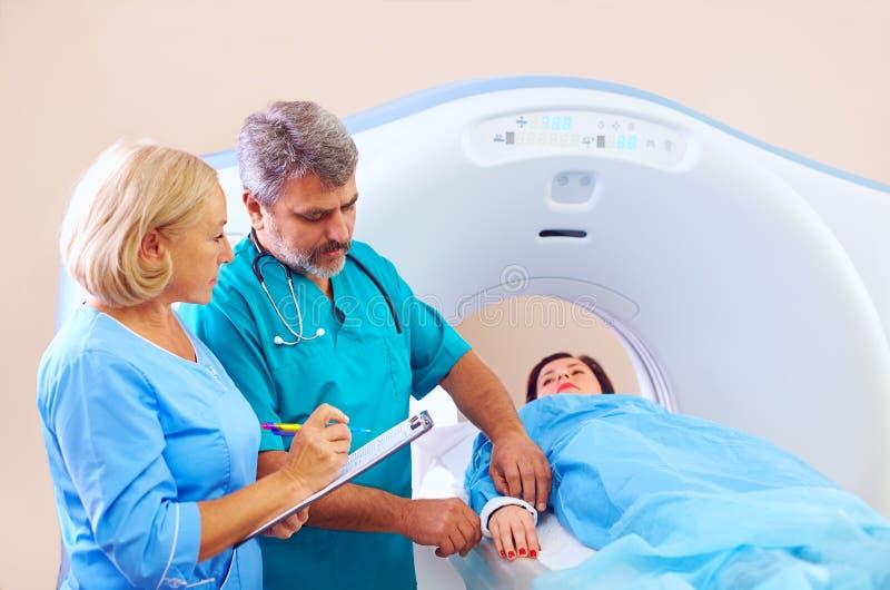 Medisch personeel dat patiënt voorbereidt aan CT scannerprocedure stock foto's