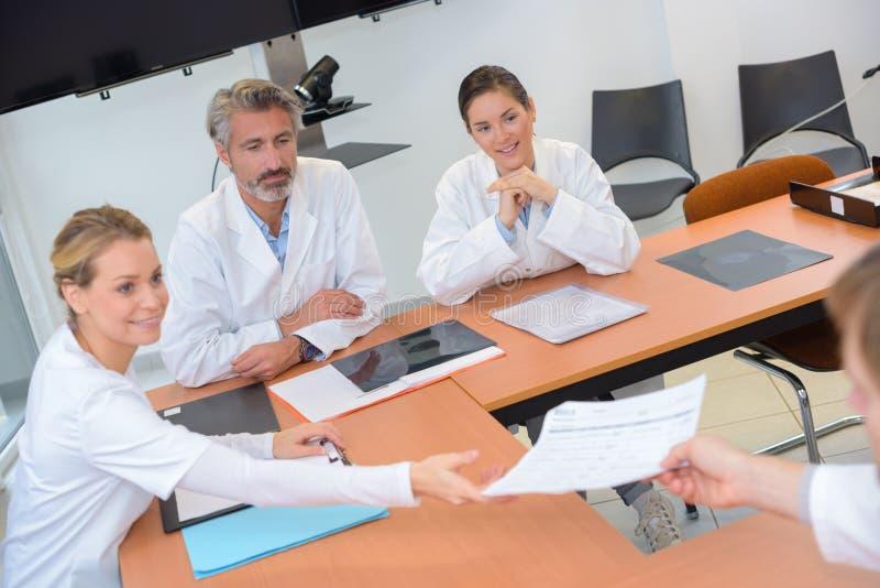 Medisch personeel die documenten in vergadering overgaan royalty-vrije stock afbeeldingen