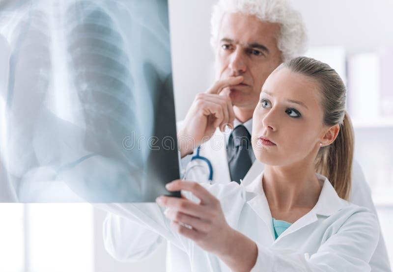 Medisch personeel die een röntgenstraal controleren stock afbeeldingen