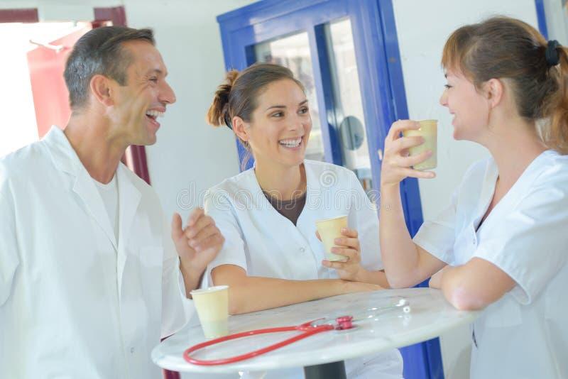 Medisch personeel die en het drinken koffie lachen royalty-vrije stock foto