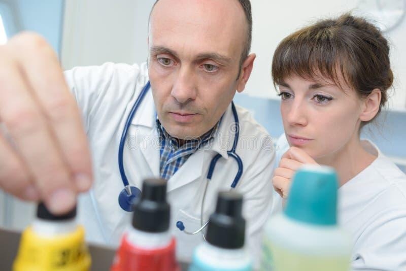 Medisch personeel die gebottelde producten bekijken stock foto's