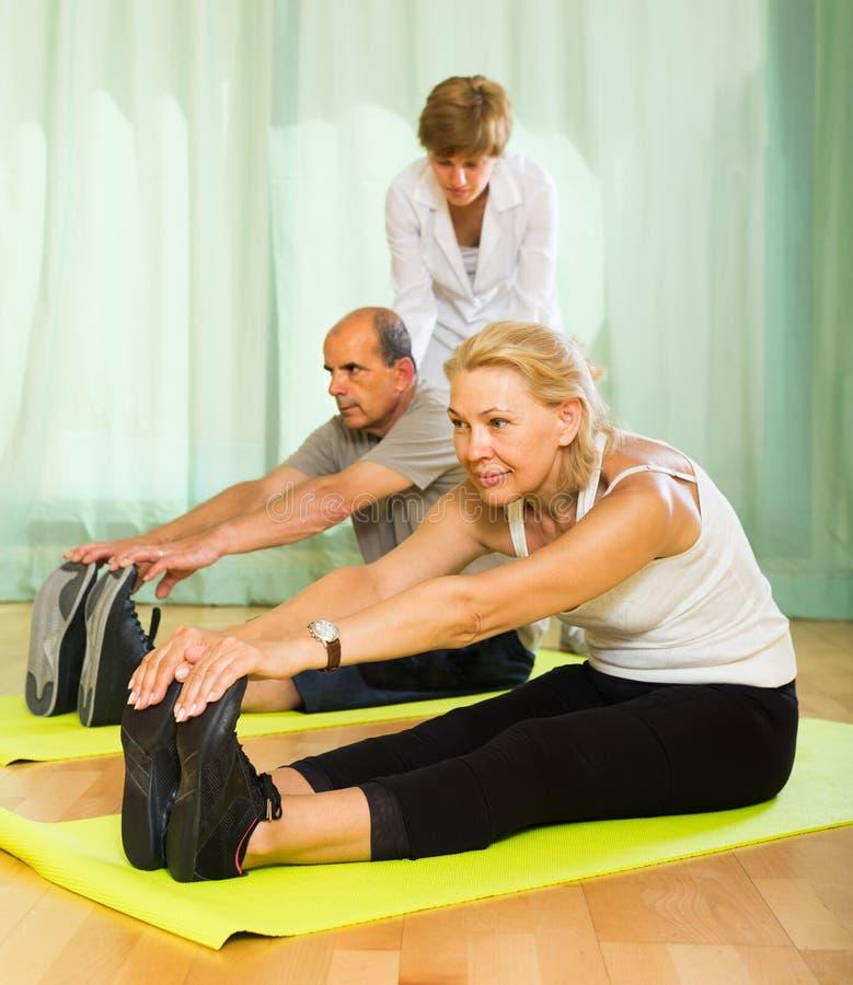 Medisch personeel met hogere mensen bij gymnastiek stock afbeelding