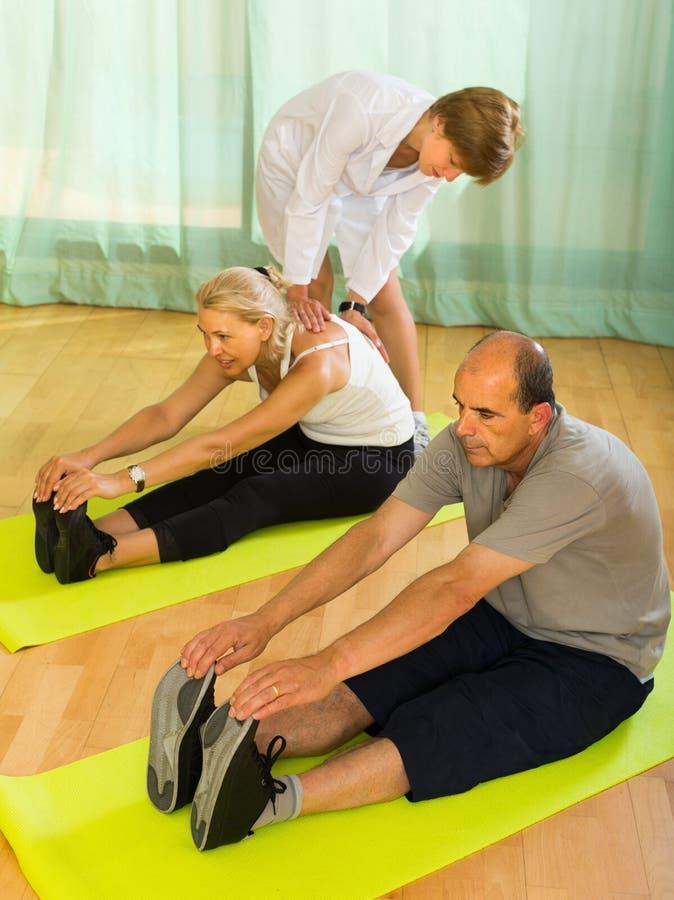 Medisch personeel met hogere mensen bij gymnastiek stock foto