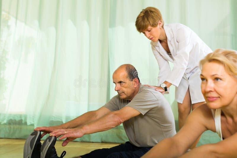 Medisch personeel met hogere mensen bij gymnastiek stock fotografie