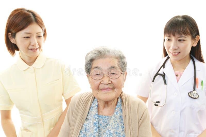 Medisch personeel met oude vrouw stock afbeelding