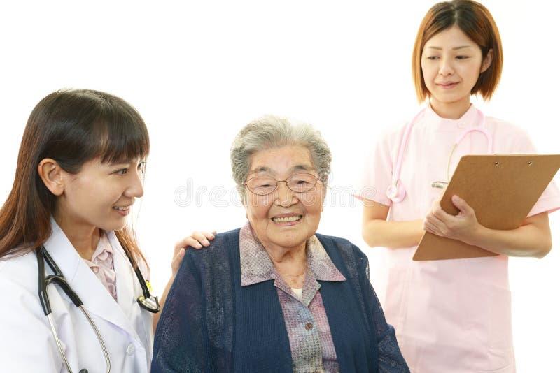 Medisch personeel met oude vrouw royalty-vrije stock foto's