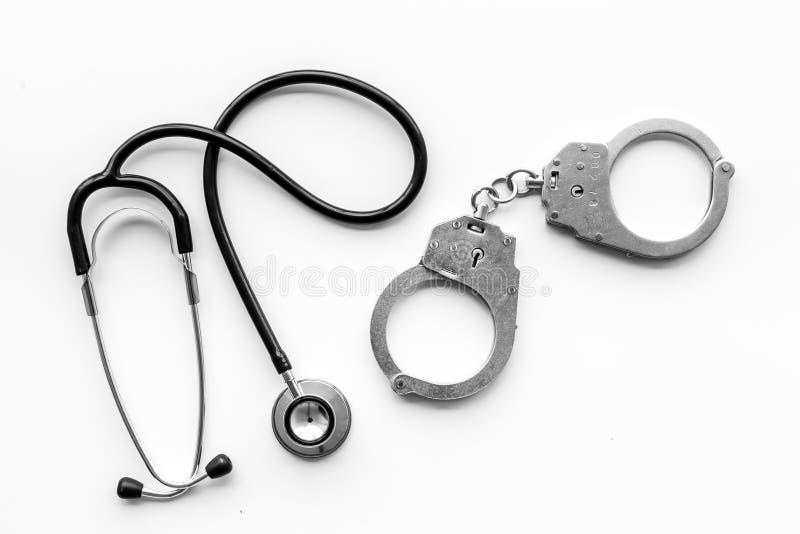 Medisch Proces Arrestatie voor medisch misdaadconcept Handcuff dichtbij stethoscoop op witte hoogste mening als achtergrond stock afbeelding