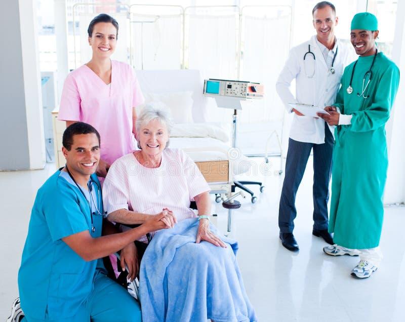 Medisch team dat een hogere vrouw behandelt stock afbeeldingen