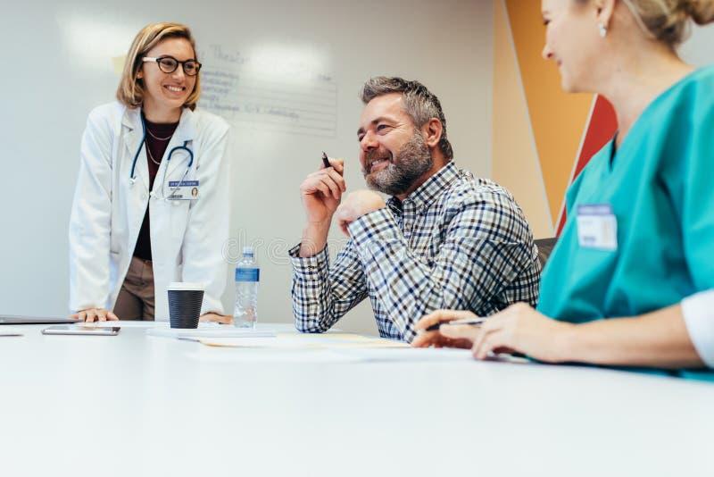 Medisch team die op een vergadering in bestuurskamer op elkaar inwerken stock afbeeldingen