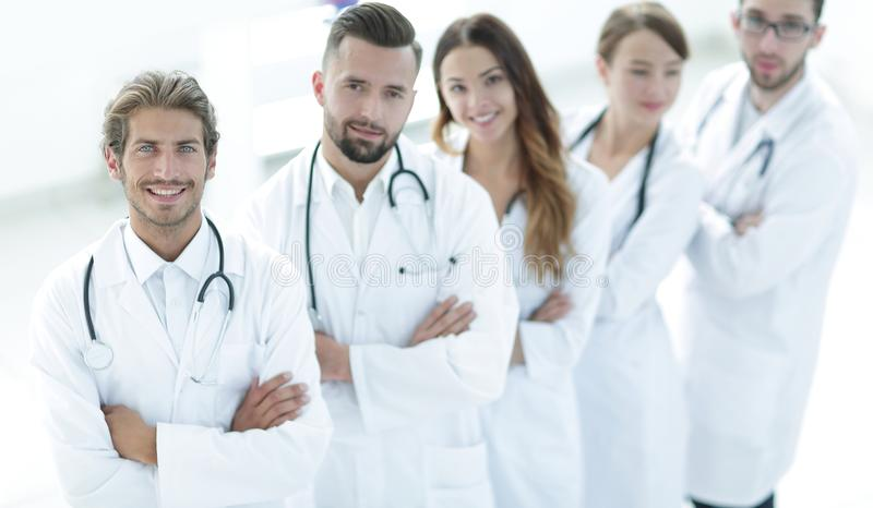 Medisch team die zich met die wapens bevinden op een witte achtergrond worden gekruist stock fotografie