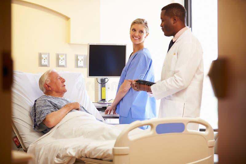 Medisch Team Meeting With Senior Man in het Ziekenhuiszaal stock afbeeldingen