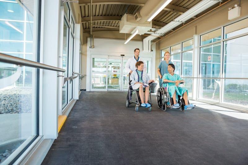 Medisch Team Pushing Patients On Wheelchairs bij royalty-vrije stock foto
