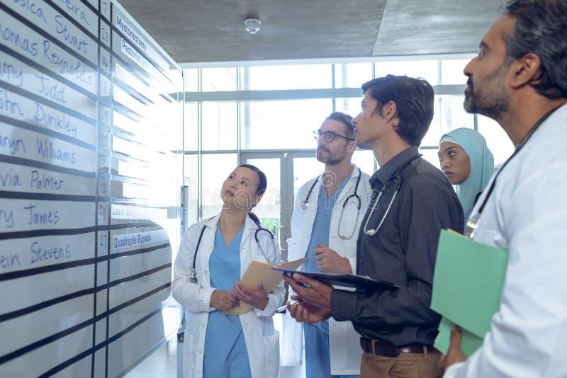 Medisch team van artsen die hun verschuivingen op grafiek bij het ziekenhuis controleren stock afbeeldingen