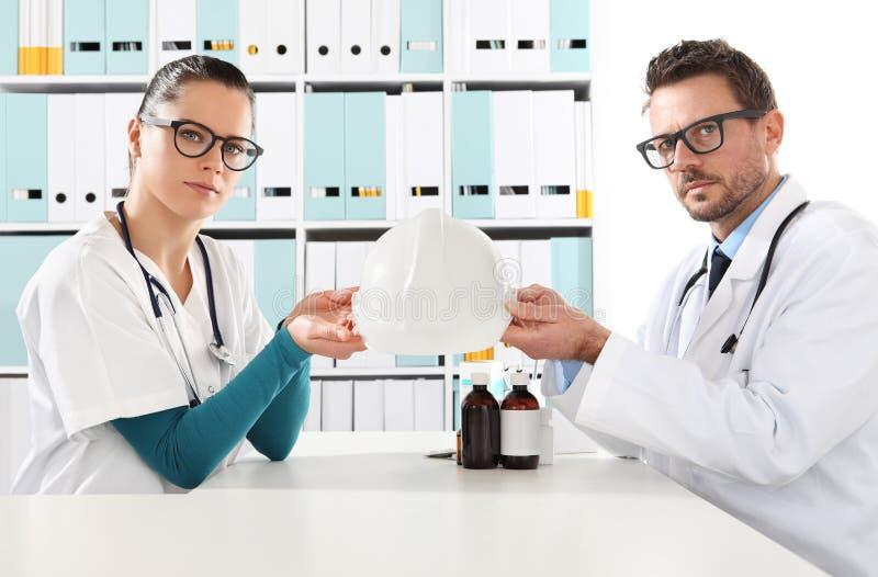 Medisch ziektekostenverzekeringconcept, artsenhanden met helm royalty-vrije stock foto