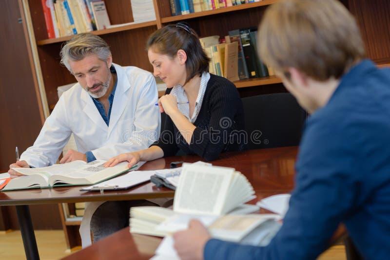 Medische arbeiders in bibliotheek stock foto