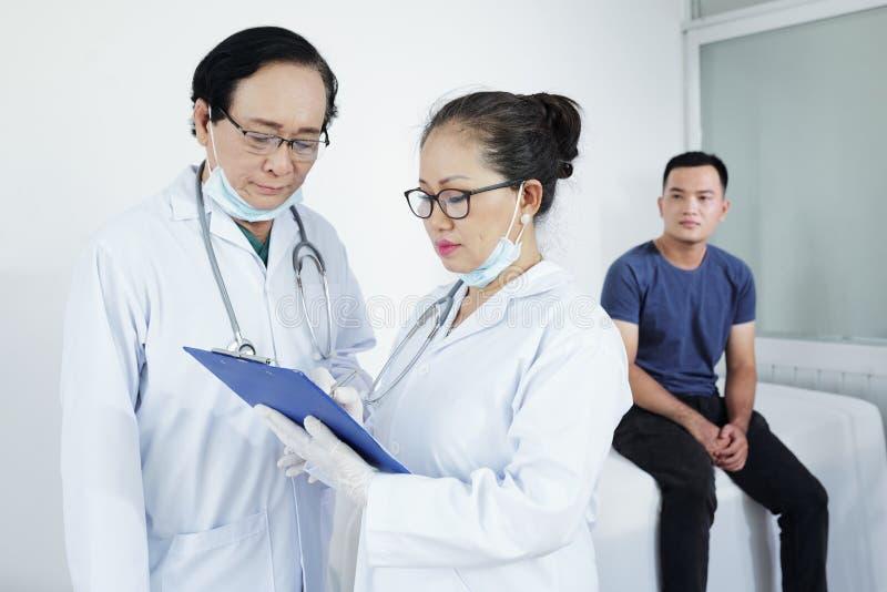 Medische arbeiders die diagnose bespreken royalty-vrije stock afbeeldingen