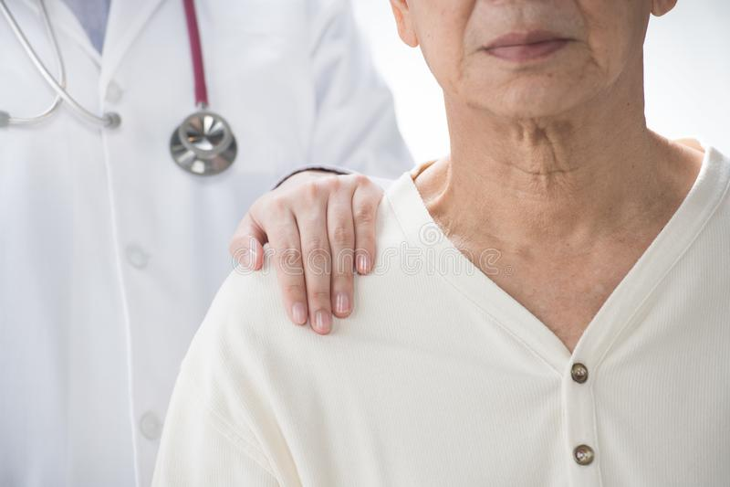 Medische arts die hogere patiënt geruststellen en een hand op patient'sschouder zetten royalty-vrije stock foto's
