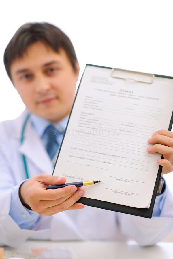 Medische arts die klembord voor u geeft aan teken stock afbeelding